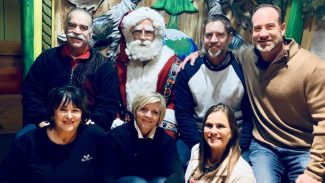 Shane Plummer with family sitting on Santa's lap for Christmas