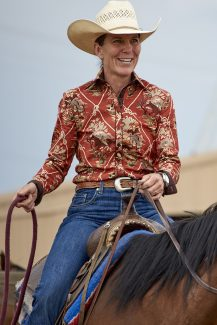 Woman riding horse wearing CR RanchWear print shirt
