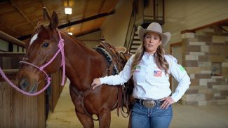 Jackie Crawford standing with horse explaining breakaway roping