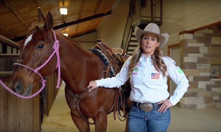 Jackie Crawford standing with horse explaining breakaway roping
