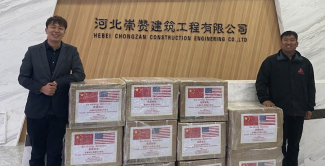 BoZhan Wei, owner of Ba Jun Heng Tong Equine Club, left, stands with boxed medical supplies.